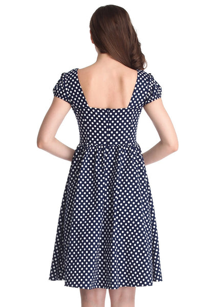 Back view of a brunette girl in a navy blue polka dot dress