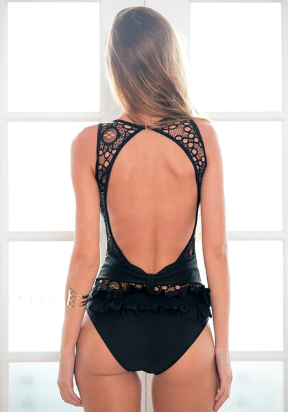 Back view of blonde model in black lace cutout open-back swimsuit