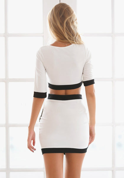 Back view of model in black-lined white two-piece dress
