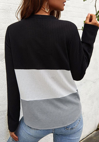 Back view of model in black V-neckline button-up tie-front colorblock waffle knit top