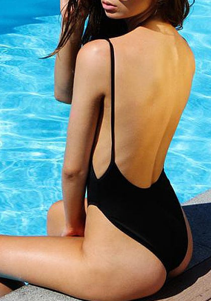 Back view of model in black classic low-back swimsuit