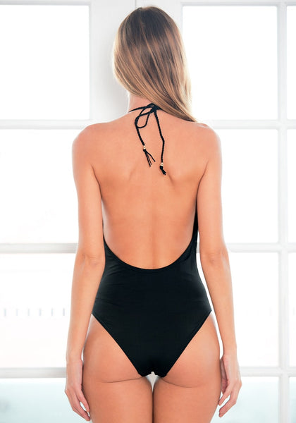 Back view of model in black lace-trim halter swimsuit