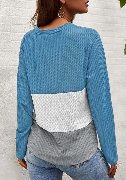 Back view of model in blue V-neckline button-up tie-front colorblock waffle knit top