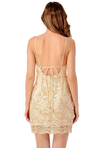 Back view of model in champagne floral embroidered scallop slip dress