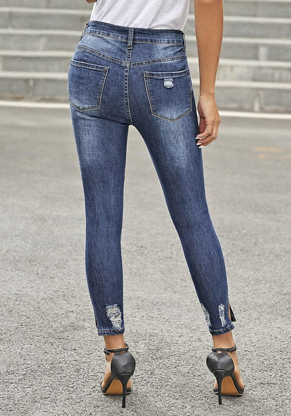 Back view of model in dark blue high-rise buttoned distressed denim skinny jeans