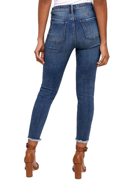Back view of model in dark blue mid-rise skinny distress denim jeans