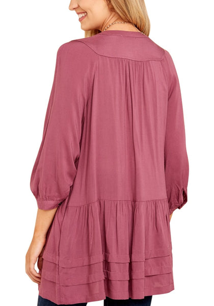 Back view of model in deep blush button-front puffed sleeves tunic