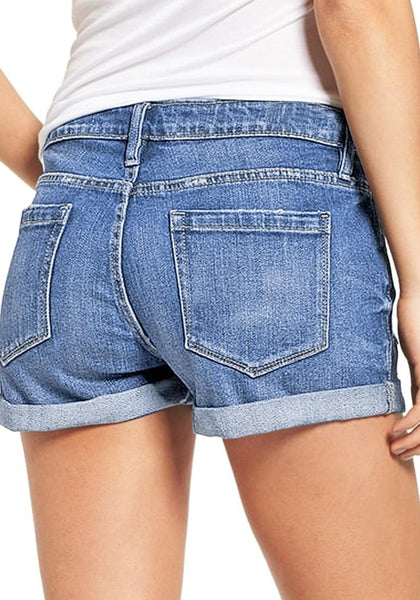 Back view of model in light blue roll-over hem button-up distressed denim shorts