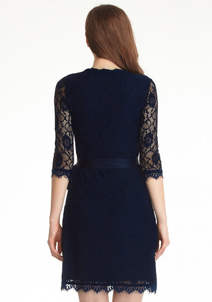 Back view of model in navy blue lace overlay plunge wrap-style dress