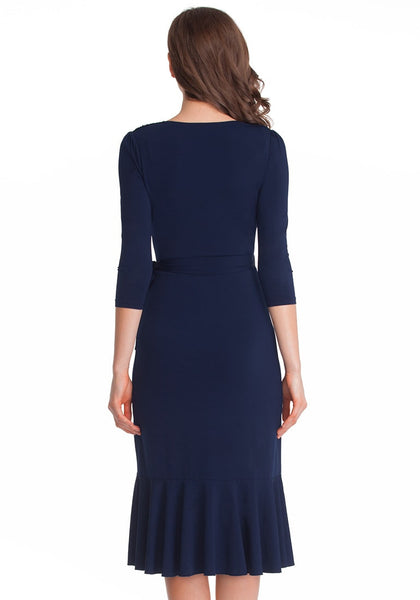 Full back shot of lady in navy blue asymmetrical ruffled wrap dress