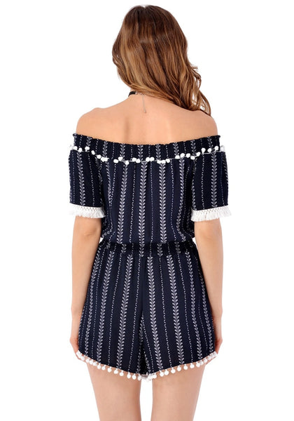 Back view of model in navy pompom off-shoulder romper