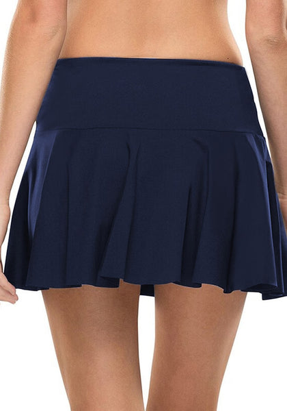 Back view of model in navy side self-tie pleated swim skirt