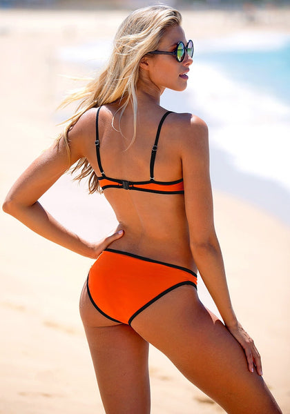 Back view of model in neon orange bikini set