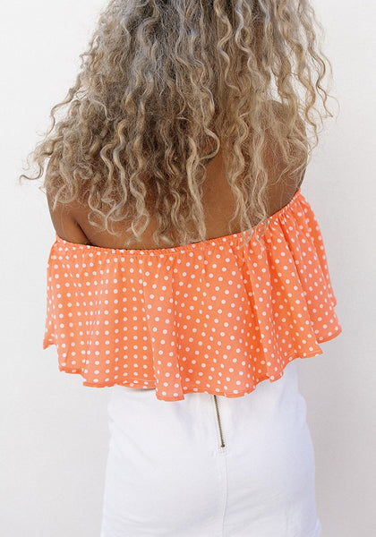Back view of model in orange polka dots off-shoulder top
