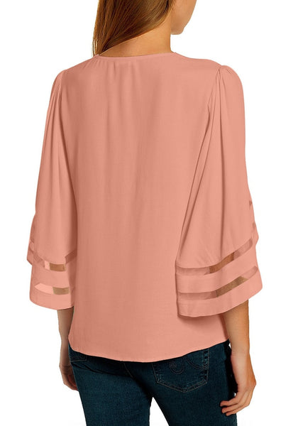 Back view of model in pink 34 bell mesh panel sleeves strappy V-neckline loose top