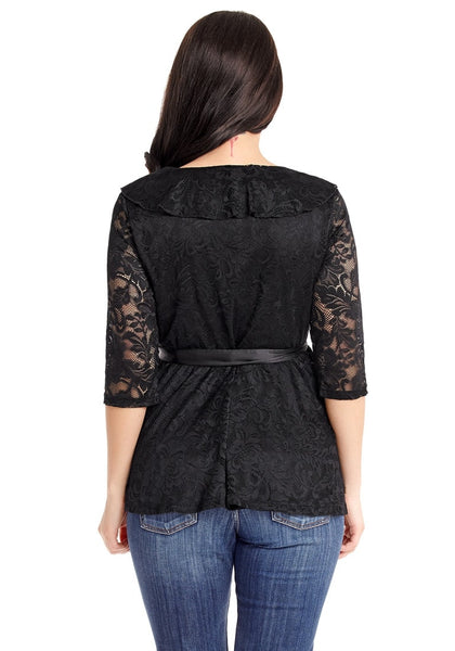 Back view of model in plus size black ruffled faux wrap blouse