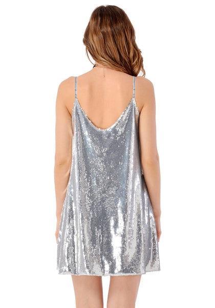 Back view of model in silver sequins slip dress