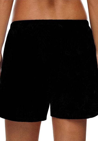 Back view of model in solid black drawstring board shorts