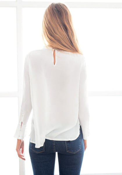 Back view of model in white asymmetric layered chiffon blouse