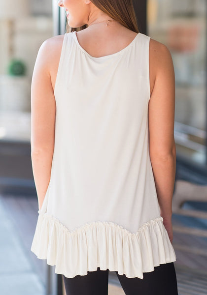 Back view of model in white ruffle-hem crew neck sleeveless tunic