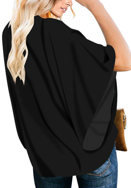 Back view of model wearing black V-neckline button-up loose kaftan top