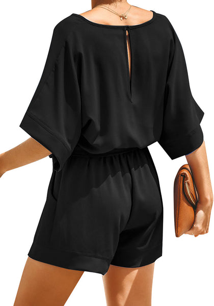 Back view of model wearing black V-neckline keyhole-back loose belted romper
