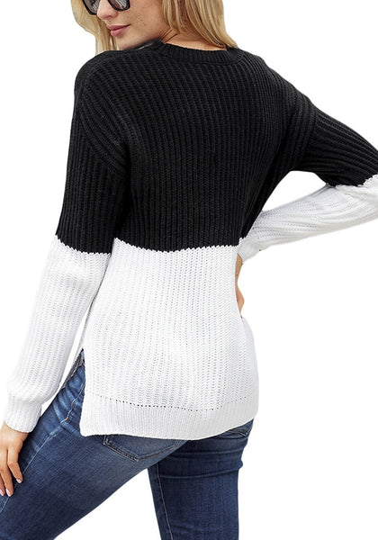Back view of model wearing black and white color block side-slit cable knit sweater