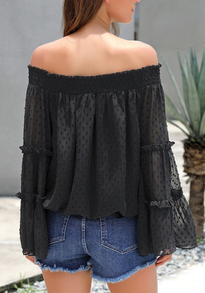 Back view of model wearing black bell sleeves dotted loose off-shoulder top