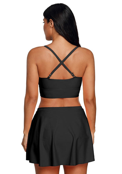 Back view of model wearing black crisscross-front two-piece skirtini set