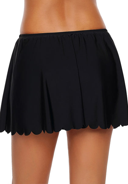 Back view of model wearing black scalloped hem swim skirt bottom