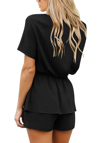 Back view of model wearing black short sleeves layer belted surplice romper