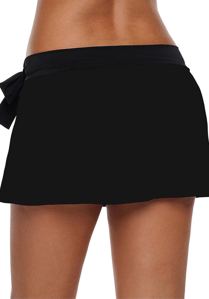 Back view of model wearing black side slit bowknot swim skirt