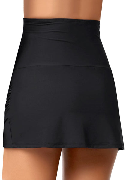 Back view of model wearing black tulip hem high waist ruched swim skirt