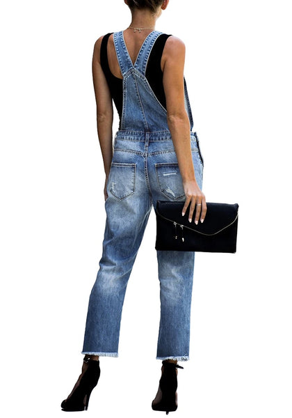 Back view of model wearing blue cropped raw hem ripped denim bib overall