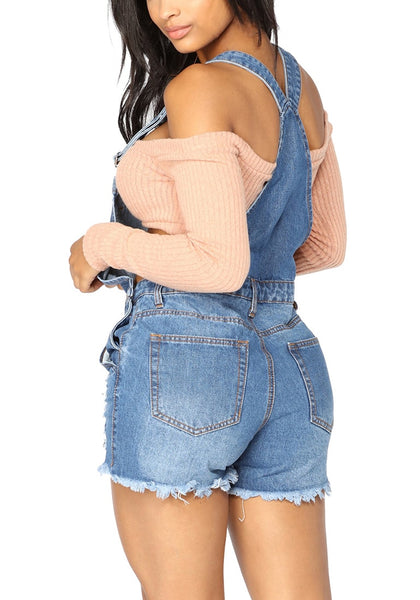 Back view of model wearing blue denim ripped shorts bib overall