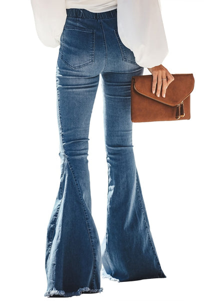 Back view of model wearing blue elastic-waist distressed denim bell bottom jeans