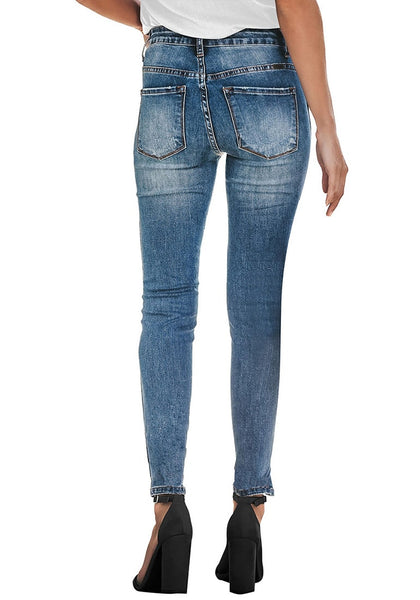 Back view of model wearing blue high-rise ripped skinny denim jeans