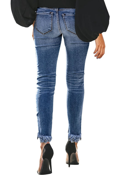 Back view of model wearing blue mid-waist raw hem  cropped ripped denim jeans