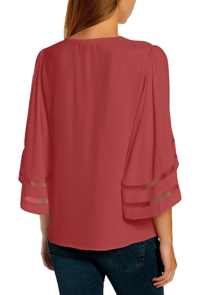 Back view of model wearing coral pink 34 bell mesh panel sleeves strappy V-neckline loose top