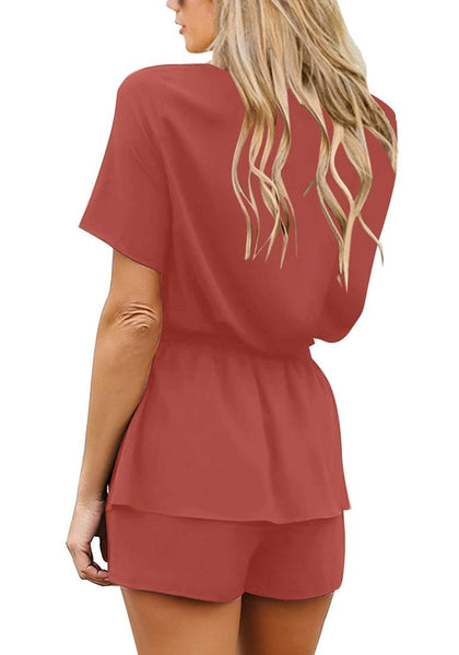 Back view of model wearing coral short sleeves layer belted surplice romper