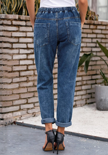 Back view of model wearing dark blue drawstring-waist cuffed ripped boyfriend jeans