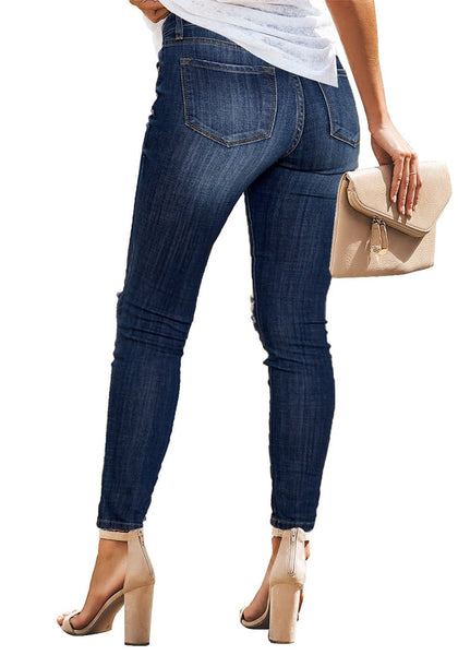 Back view of model wearing dark blue mid-rise ripped denim skinny jeans