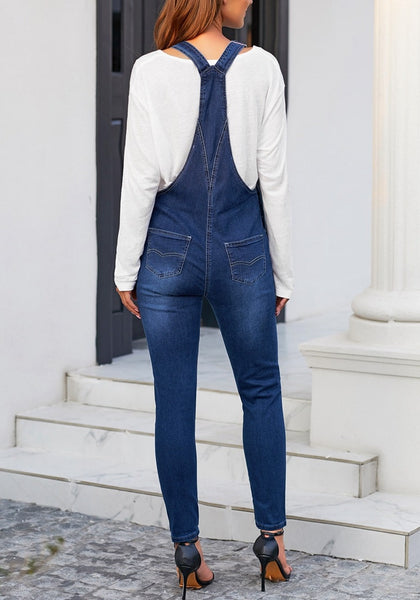 Back view of model wearing dark blue rolled hem skinny denim bib overall jumpsuit