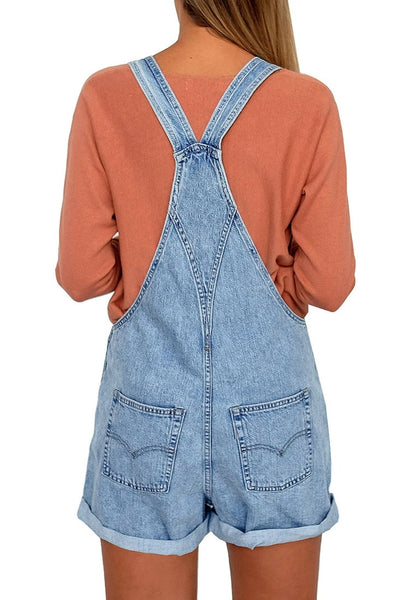 Back view of model wearing light blue button-front rolled hem shorts denim overall