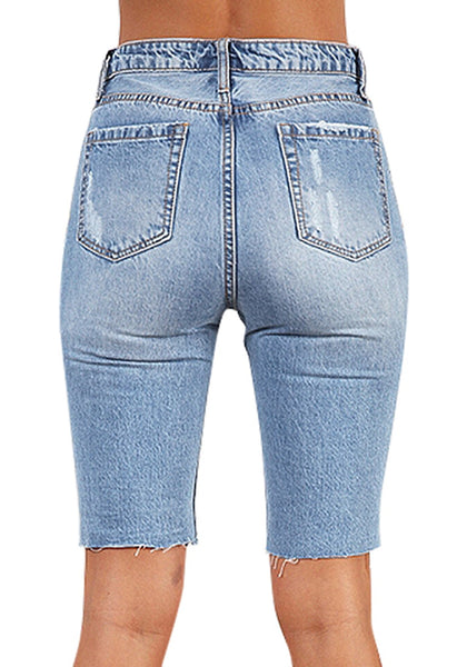 Back view of model wearing light blue ripped knee-length washed jeans shorts