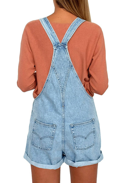 Back view of model wearing light blue rolled hem shorts denim bib overall