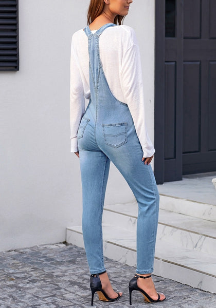 Back view of model wearing light blue rolled hem skinny denim bib overall jumpsuit