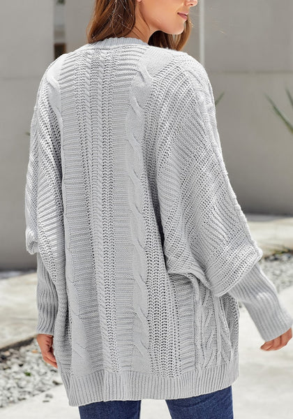 Back view of model wearing light grey open-front oversized cable knit cardigan