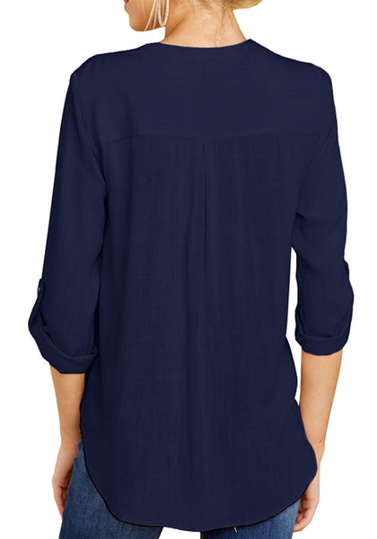 Back view of model wearing navy blue V-neckline cuffed sleeves loose surplice top