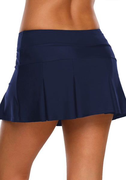 Back view of model wearing  navy blue pleated mid-waist skirt